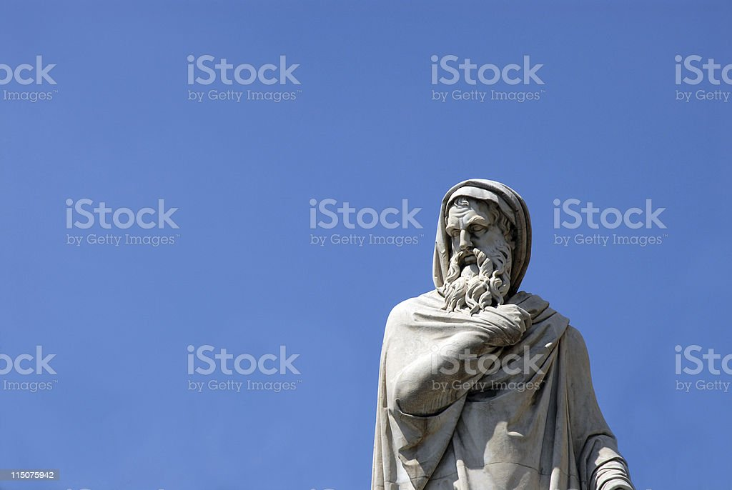 A gray statue of a wise man against a blue sky stock photo
