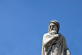 A gray statue of a wise man against a blue sky