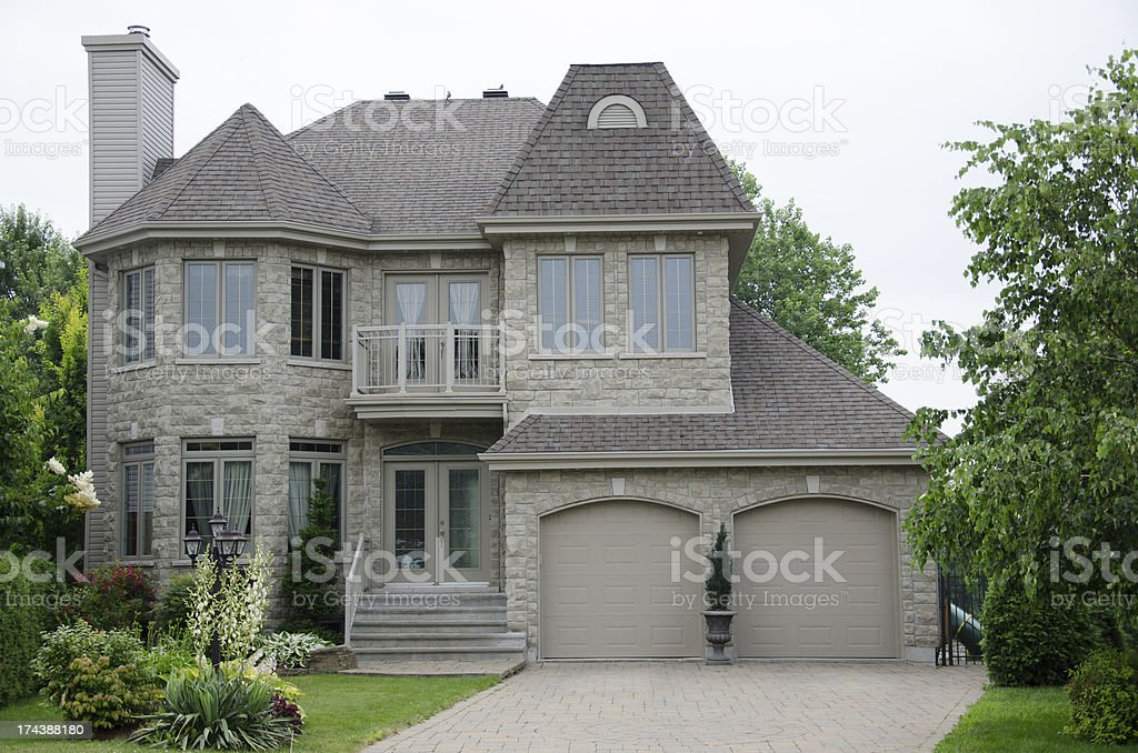 Gray stone luxury house surrounded by trees royalty-free stock photo