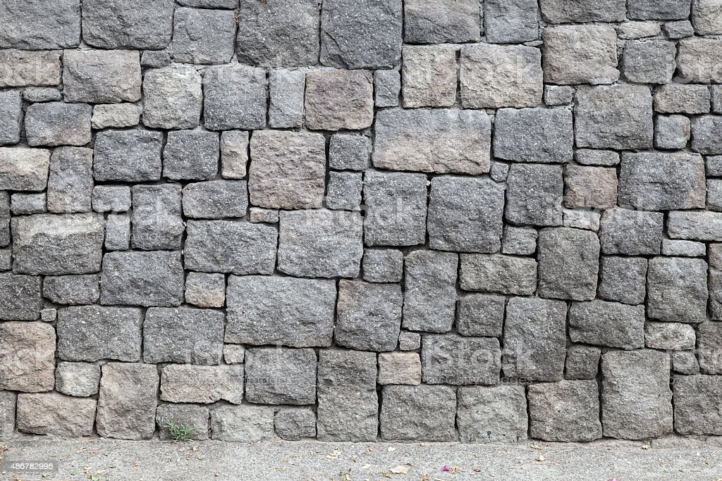Gray stone wall and road, background texture stock photo