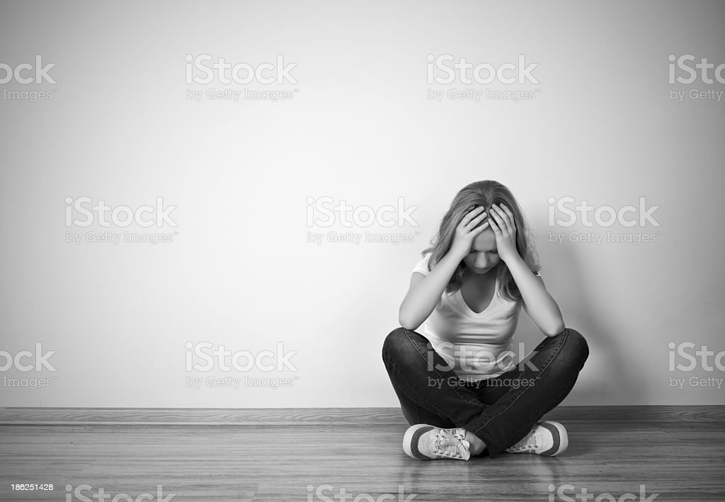 Gray-scale girl sits against wall with head down stock photo