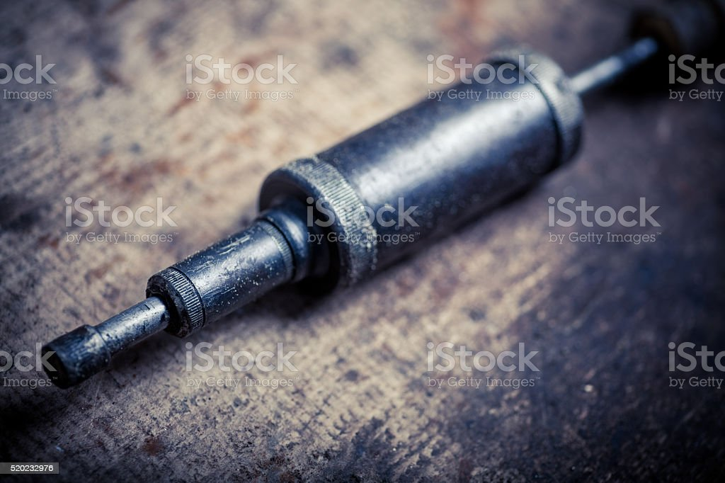 Grease pump on wooden plank stock photo