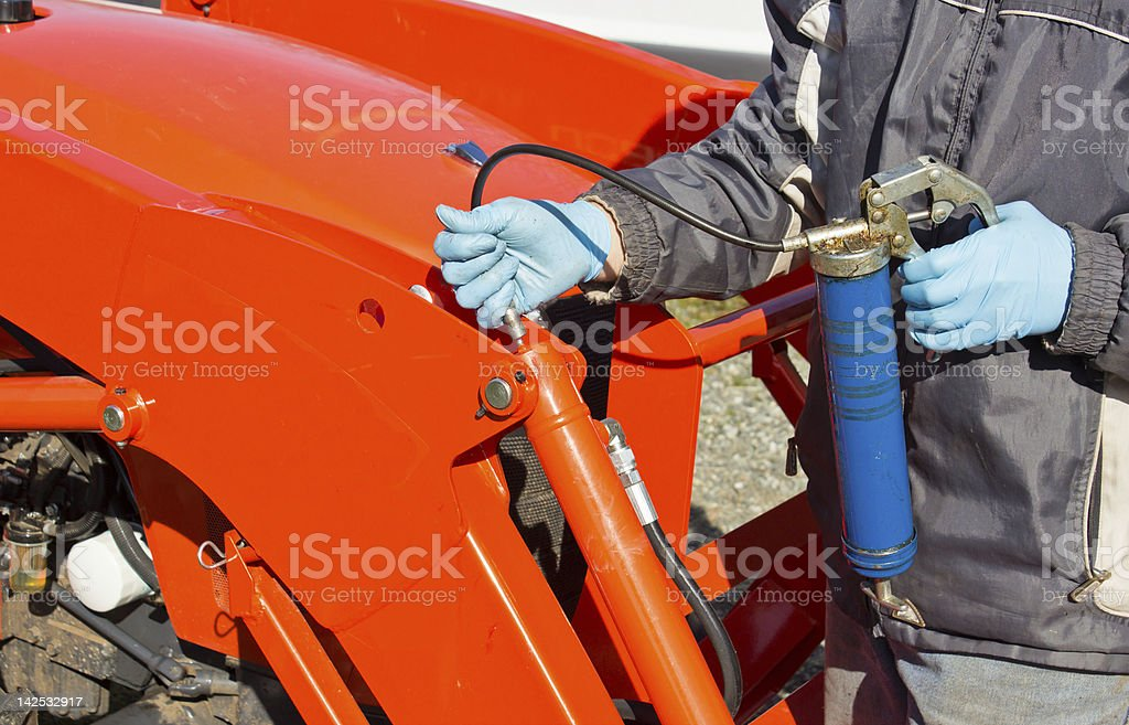 Greasing Tractor Piston stock photo