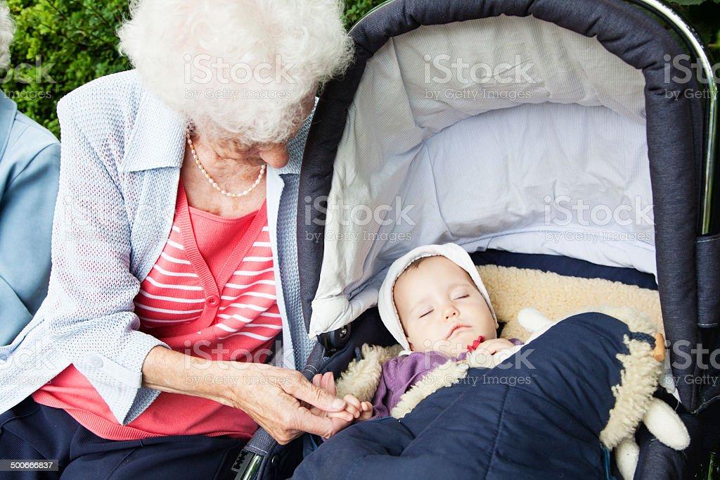 great grandmother and sleeping baby girl stock photo