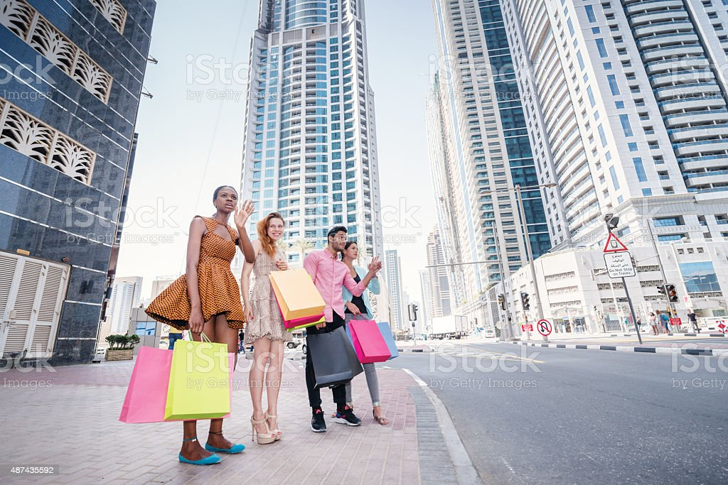 Great shopping. Four friends holding shopping bags in their hand stock photo