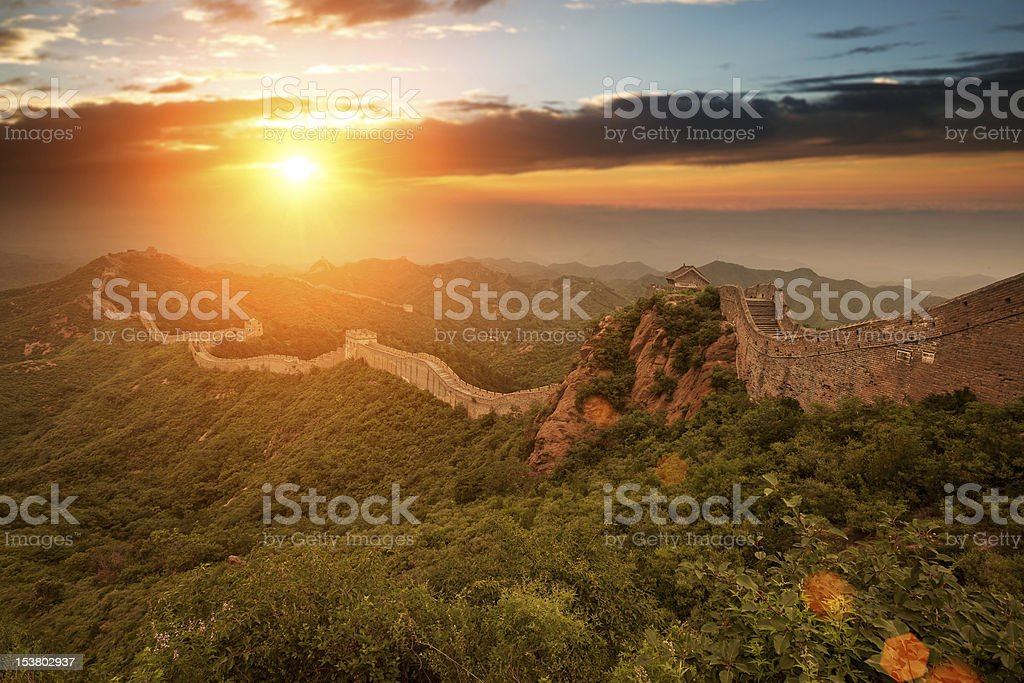Great Wall of China surrounded by dense forests at sunrise stock photo