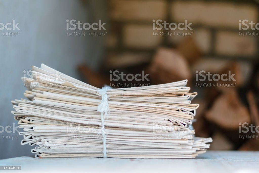 Greater pack of newspapers on a table with a rope stock photo