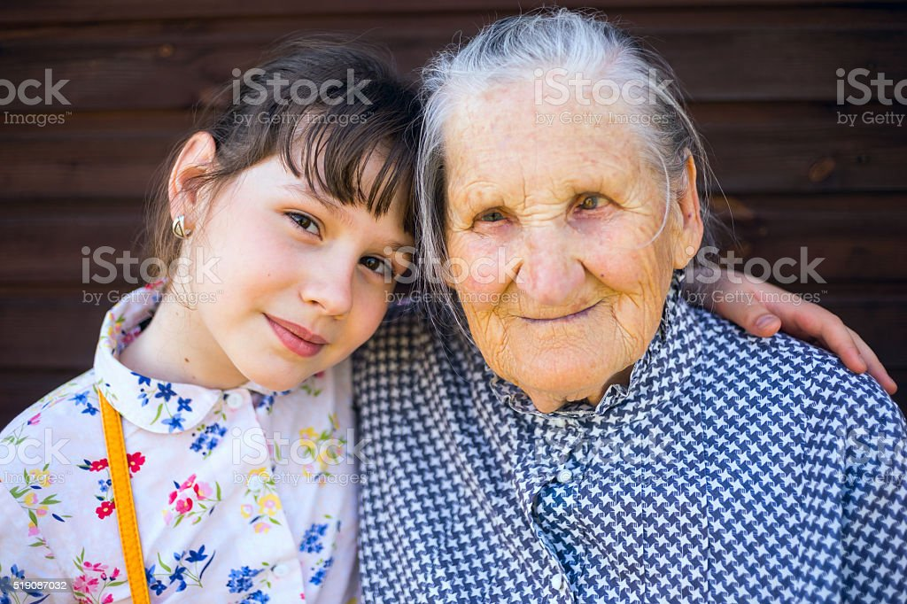 Great-grandmother, and great-granddaughter sitting arm  in arm. stock photo
