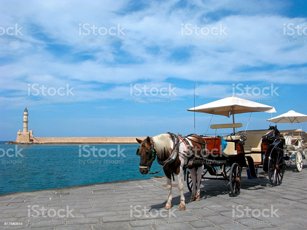 Greece, Crete. Venetian lighthouse and horse with cart in Chania. stock photo