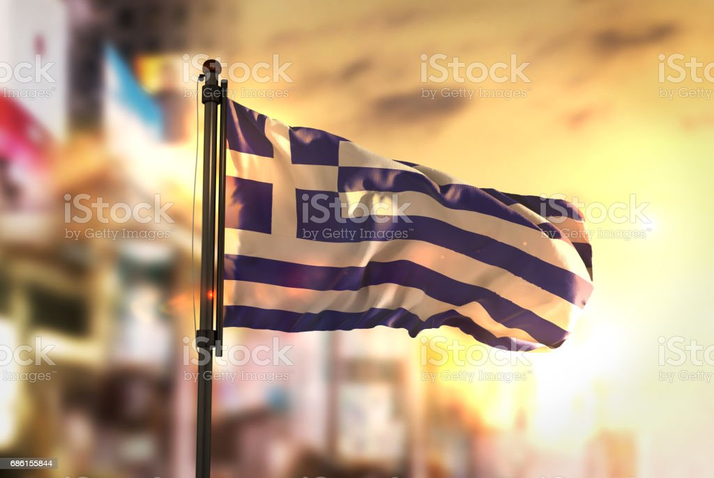 Greece Flag Against City Blurred Background At Sunrise Backlight stock photo