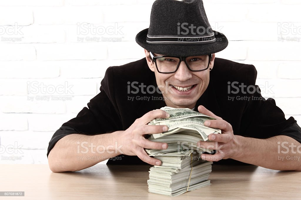 Greed emotional man in glasses holding bundles of money stock photo