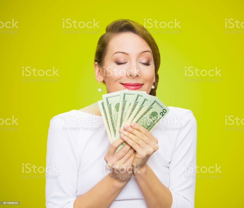 greedy executive, CEO, boss, corporate employee, holding, smelling dollar banknotes tightly, stock photo