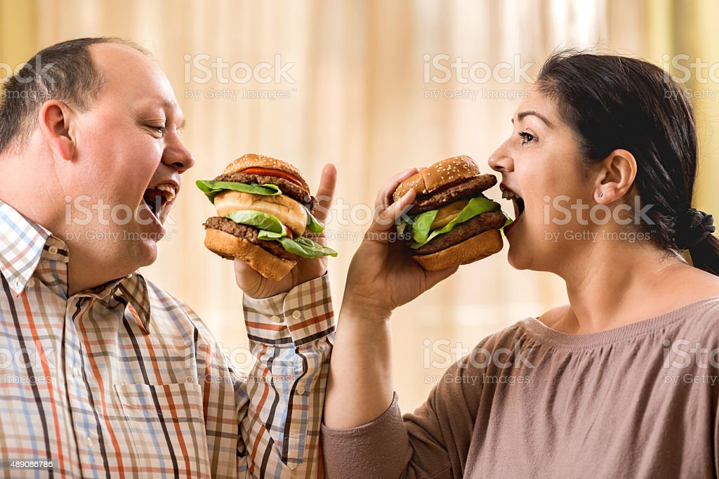 Greedy fat couple eating burgers. stock photo