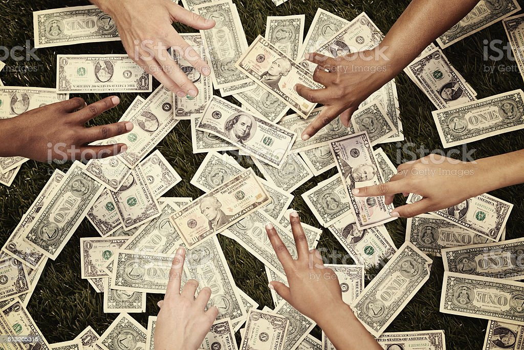 Greedy hands grabbing dollars on grassy background stock photo