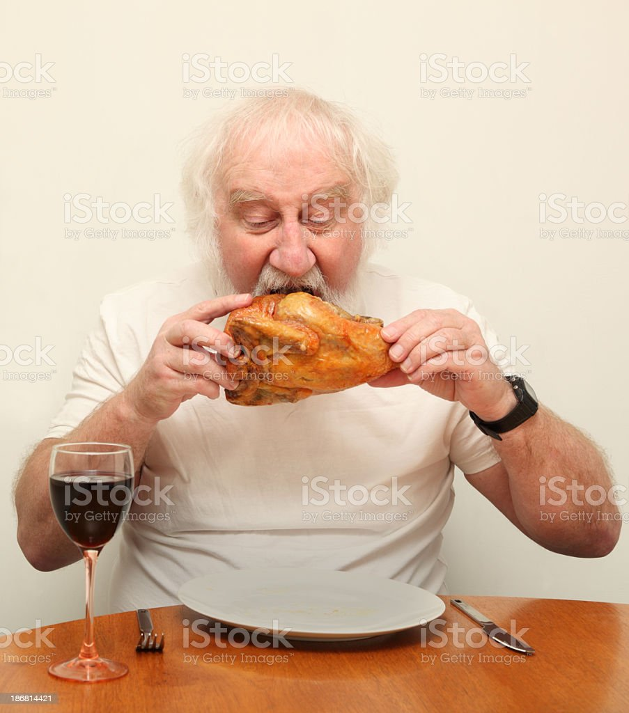 greedy senior bearded male eating whole roast chicken with intensity royalty-free stock photo