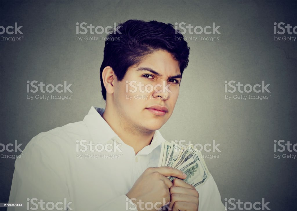 Greedy suspicious man holding money dollar bills in hand stock photo