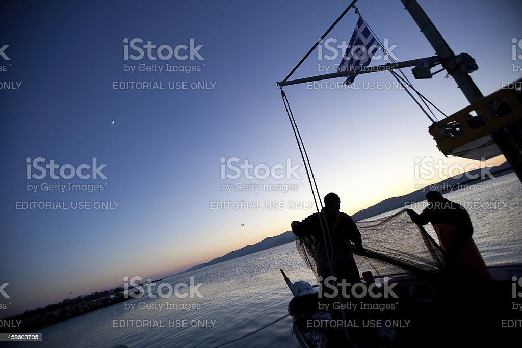 Greek Fishermen bringing in the nets at sunset royalty-free stock photo