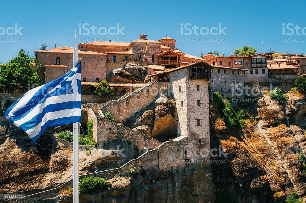 Greek flag against The Holy Monastery of Great Meteoron, Greece стоковое фото
