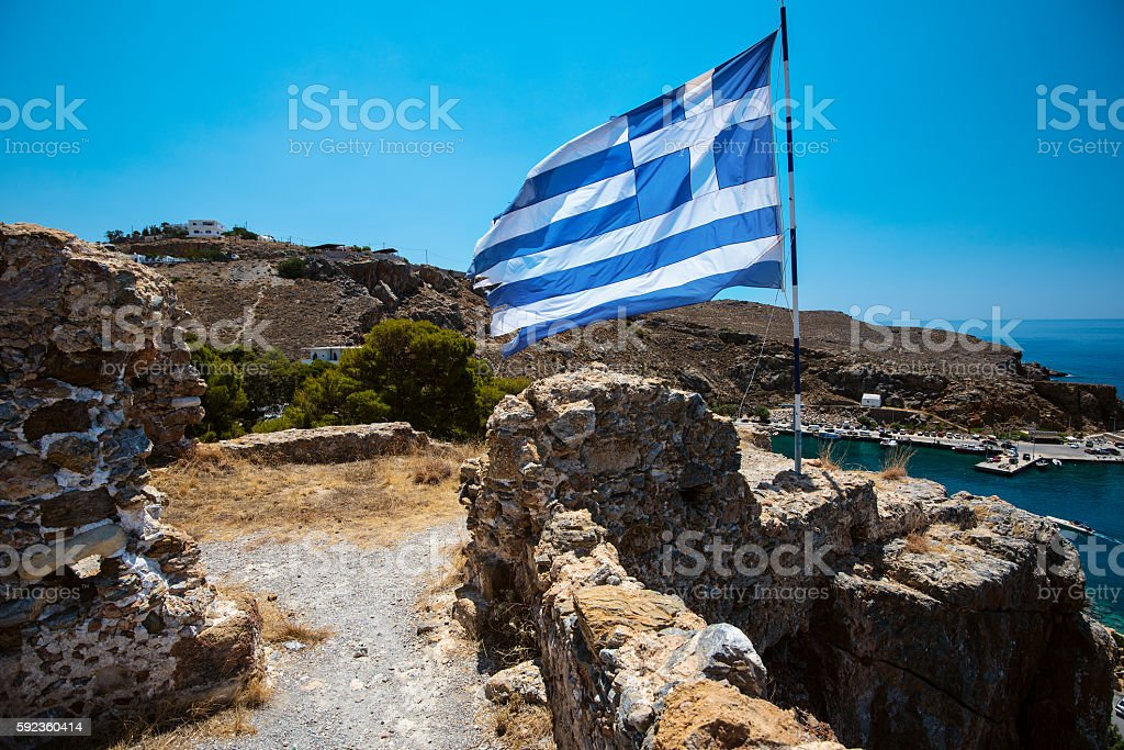 Greek flag on hill with ancient ruins on Crete island stock photo