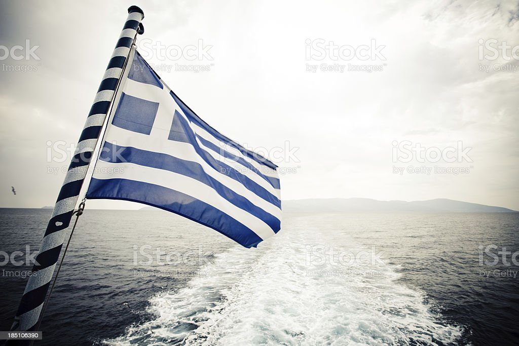 Greek flag sailing away from the mainland royalty-free stock photo