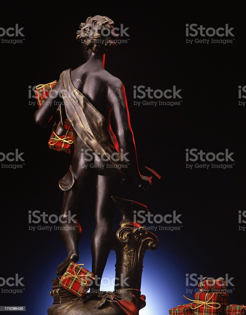 Greek god figurine holding Christmas presents royalty-free stock photo