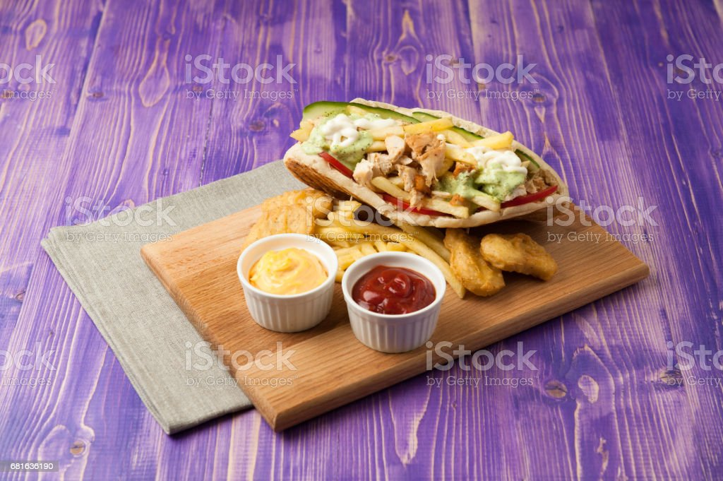 Greek gyros with fries and nuggets on a wooden board with two cups of sauce on the table stock photo