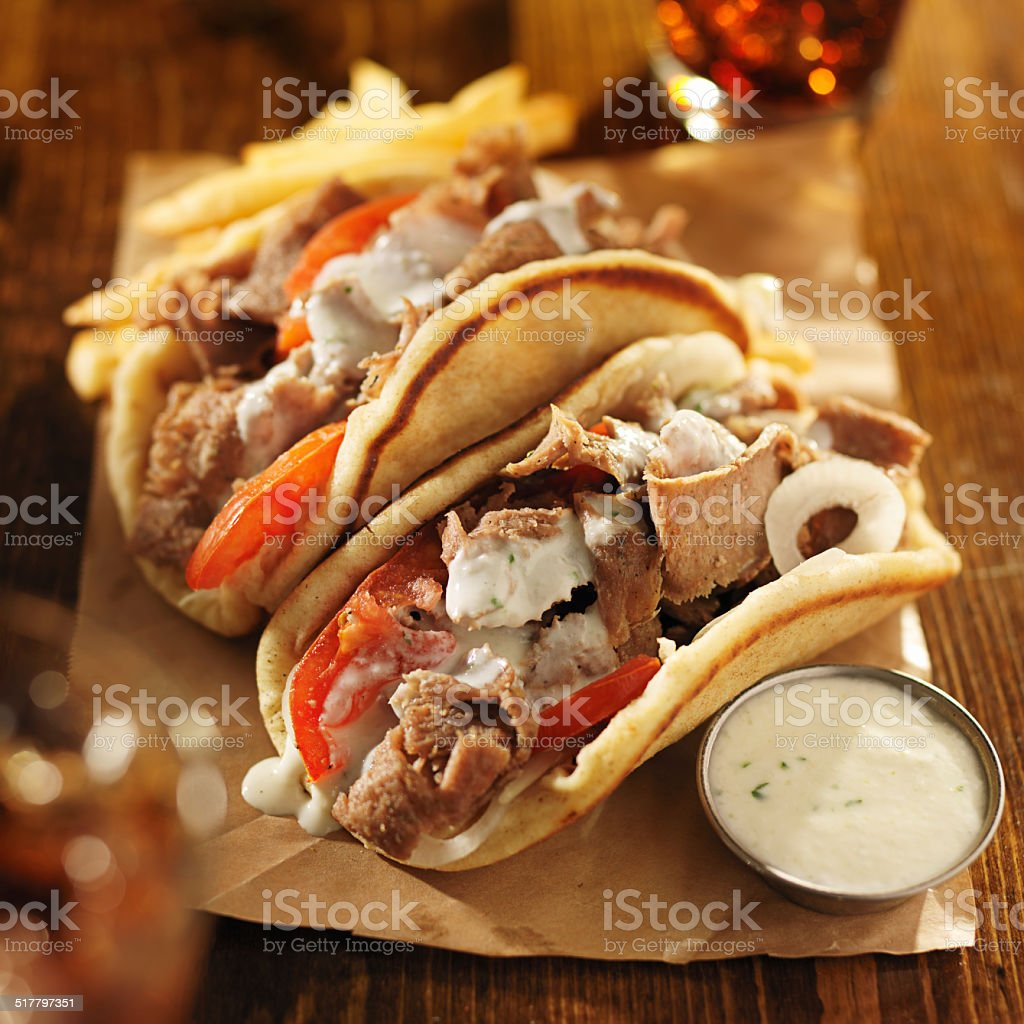 greek gyros with tzatziki sauce, cola and fries stock photo