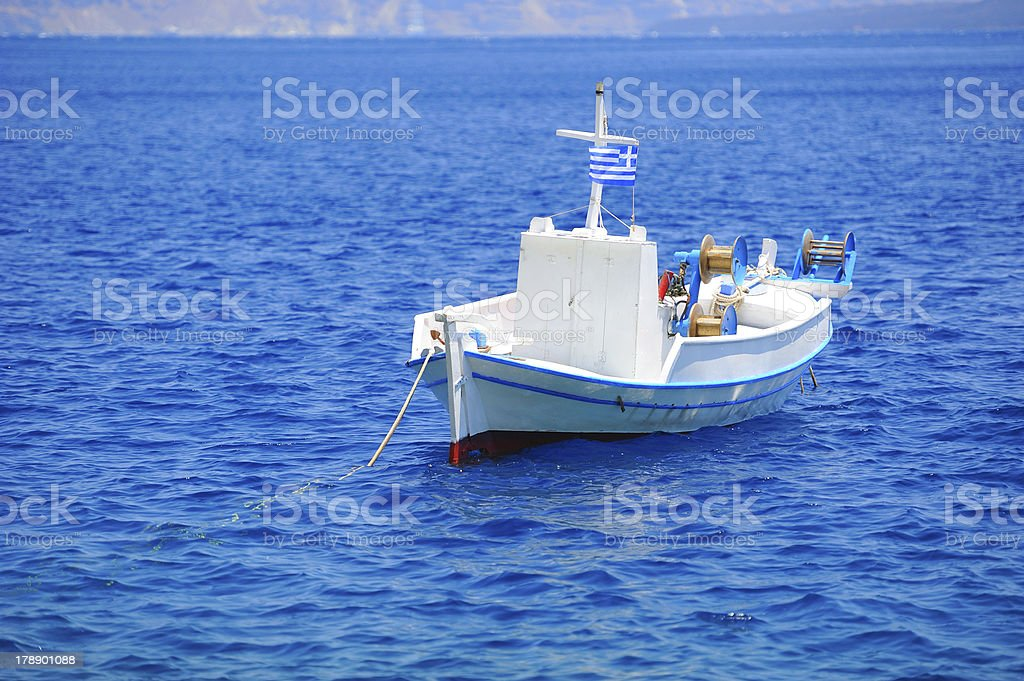 Greek landscape with a white fishing boat (Santorini island) royalty-free stock photo