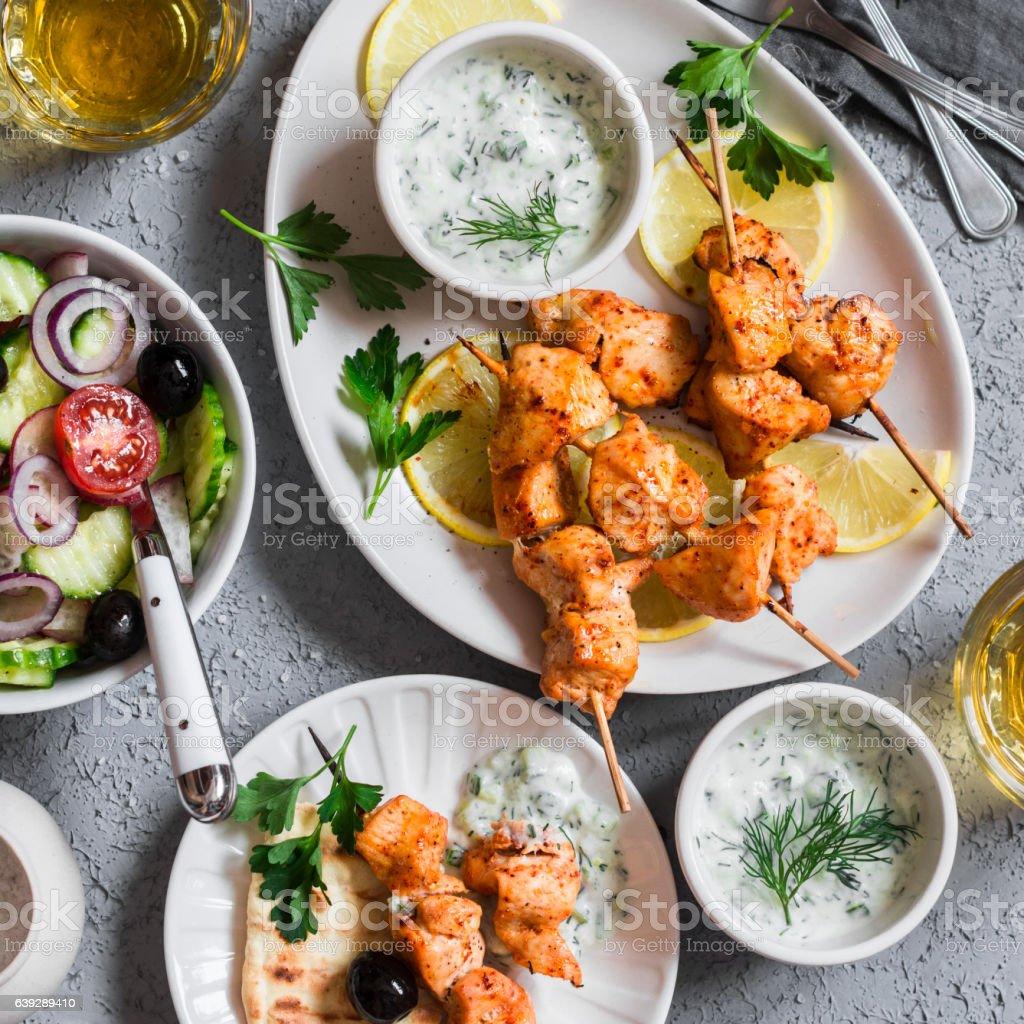 Greek lunch - chicken kebabs, salad, tzatziki, flatbreads, white wine stock photo