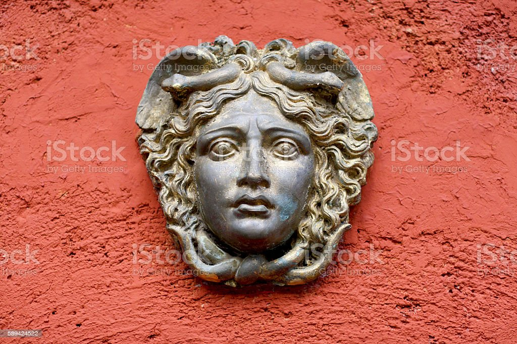 Greek / Roman Woman Face on a red painted wall stock photo