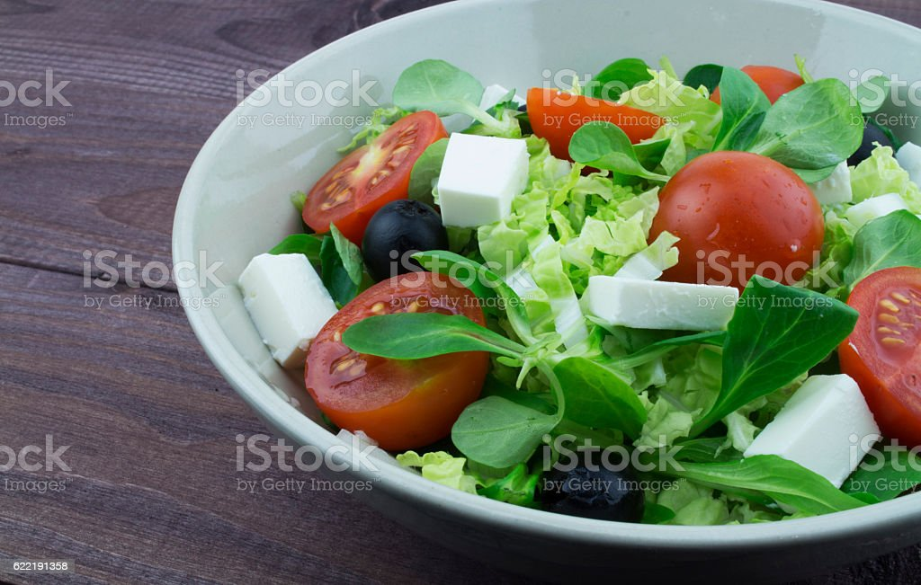 Greek salad in a plate on a dark wooden background royalty-free stock photo