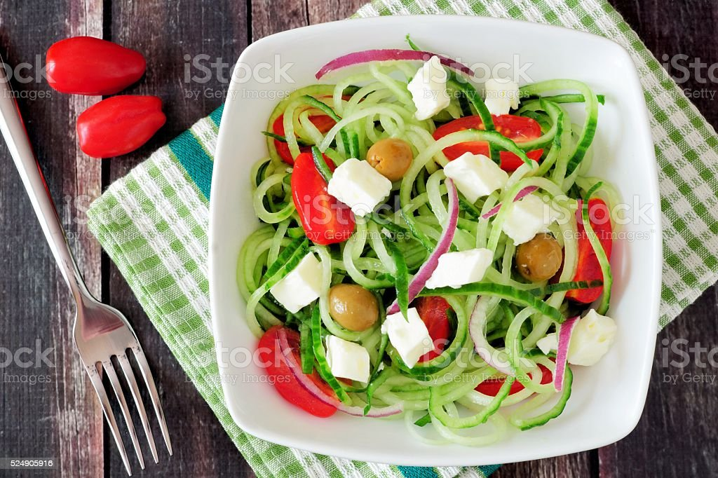 Greek Salad with cucumber noodles above view on dark wood stock photo