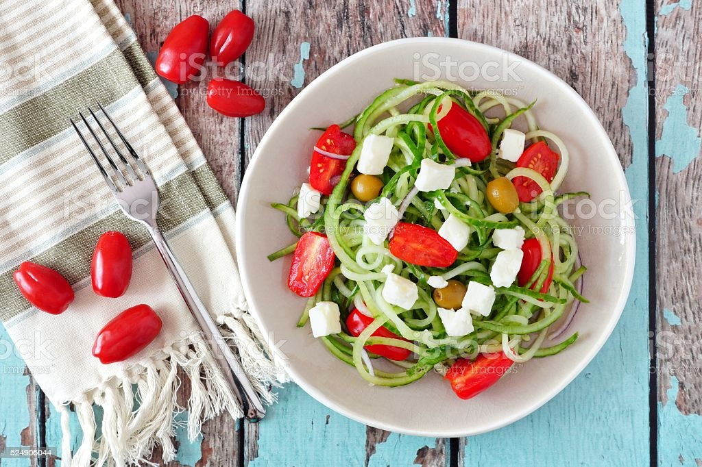 Greek Salad with cucumber noodles, overhead scene on rustic wood stock photo