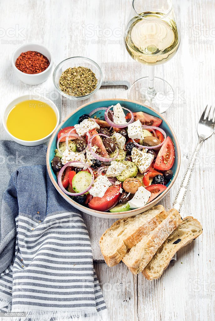 Greek salad with olive oil, bread slices, spices, white wine stock photo