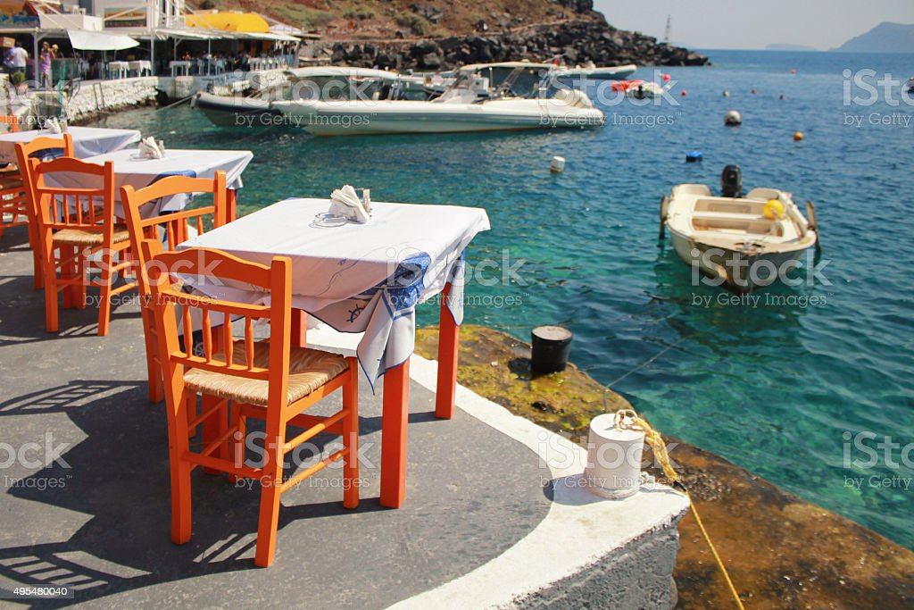 greek tavern with orange chairs by sea coast, Greece stock photo