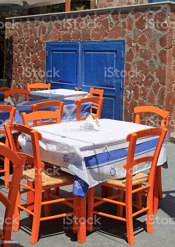 greek tavern with orange wooden chairs by sea coast, Greece stock photo