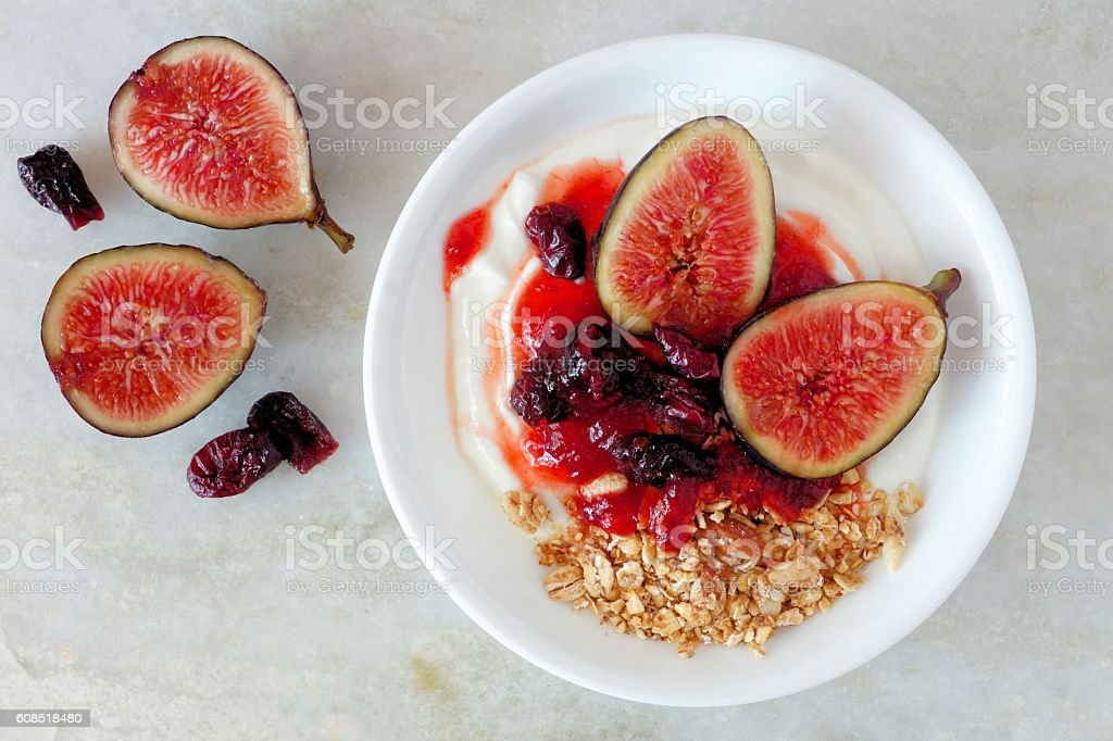 Greek yogurt with sweet figs, berries and granola on marble stock photo