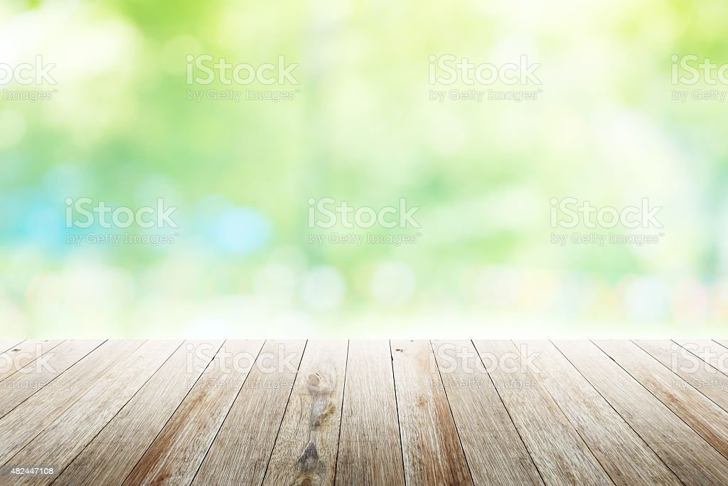 Green abstract blur nature background with wooden floor stock photo