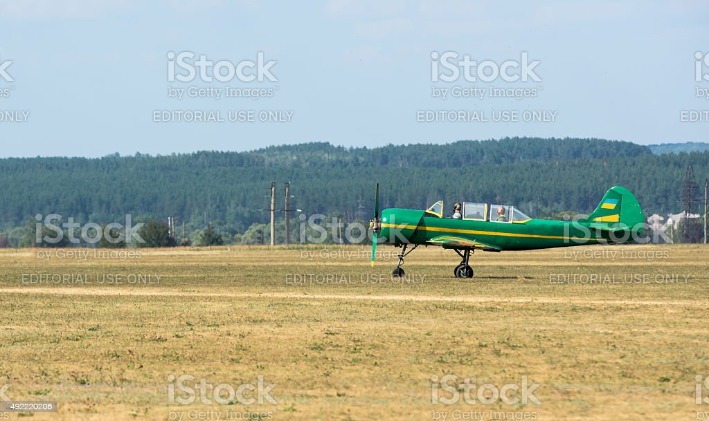 green airplane with propeller on airfield stock photo