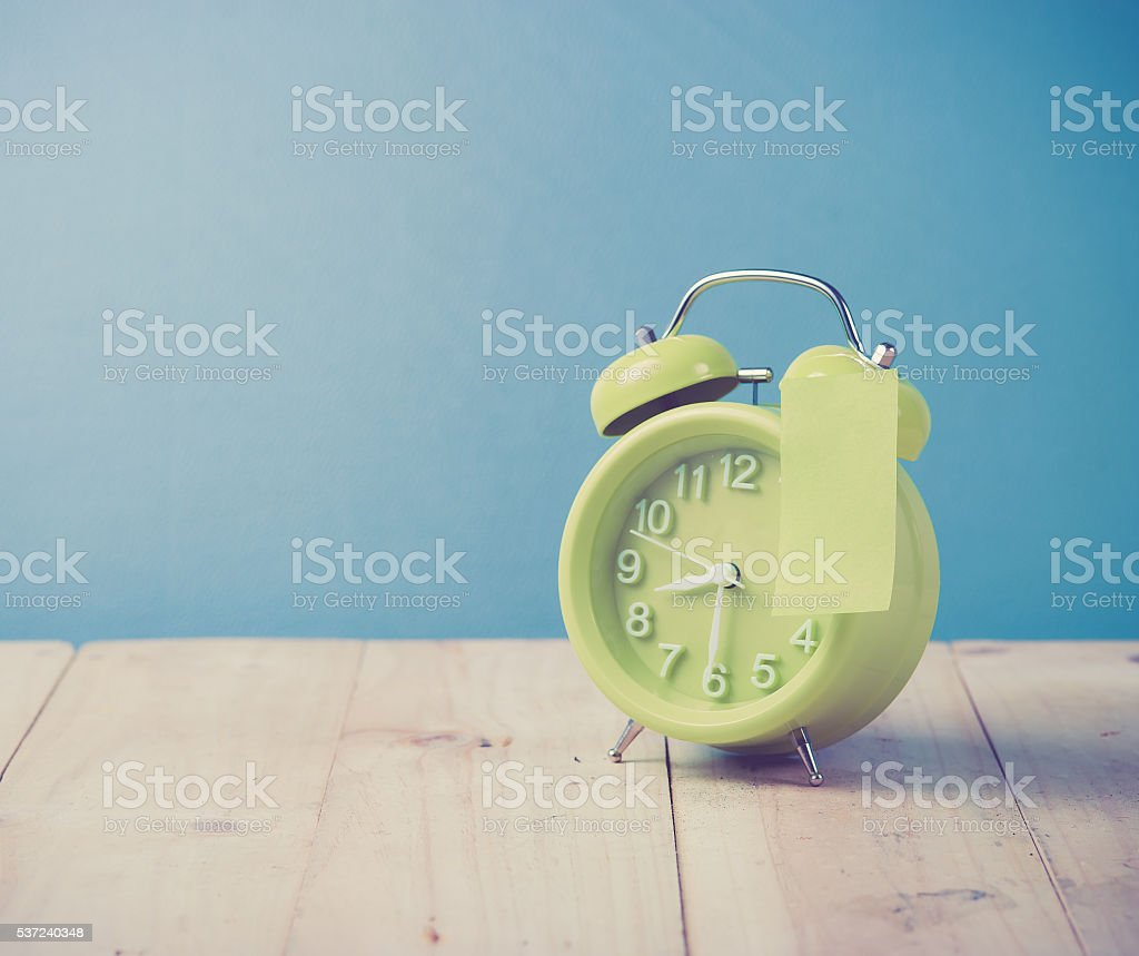Green alarm clock and sticky paper stock photo