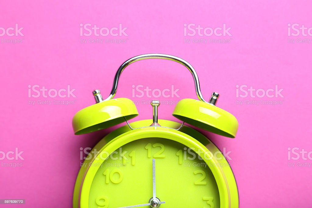 Green alarm clock on a pink background stock photo