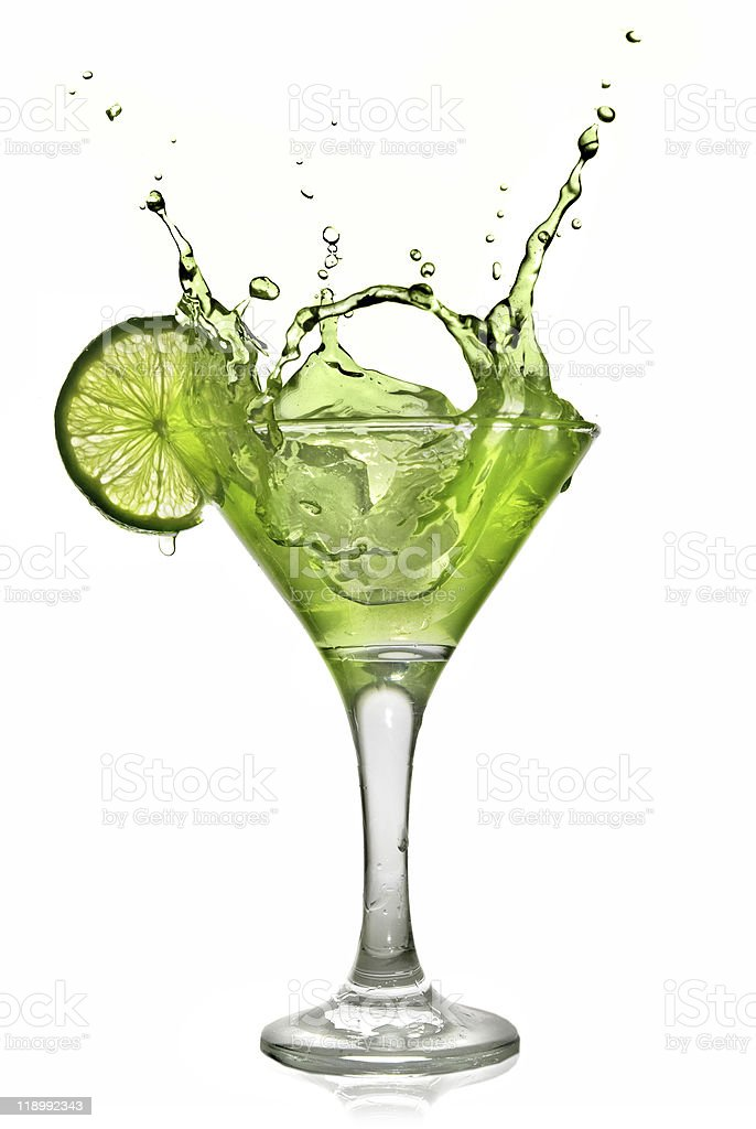 Green alchohol cocktail with lime and splash on white stock photo