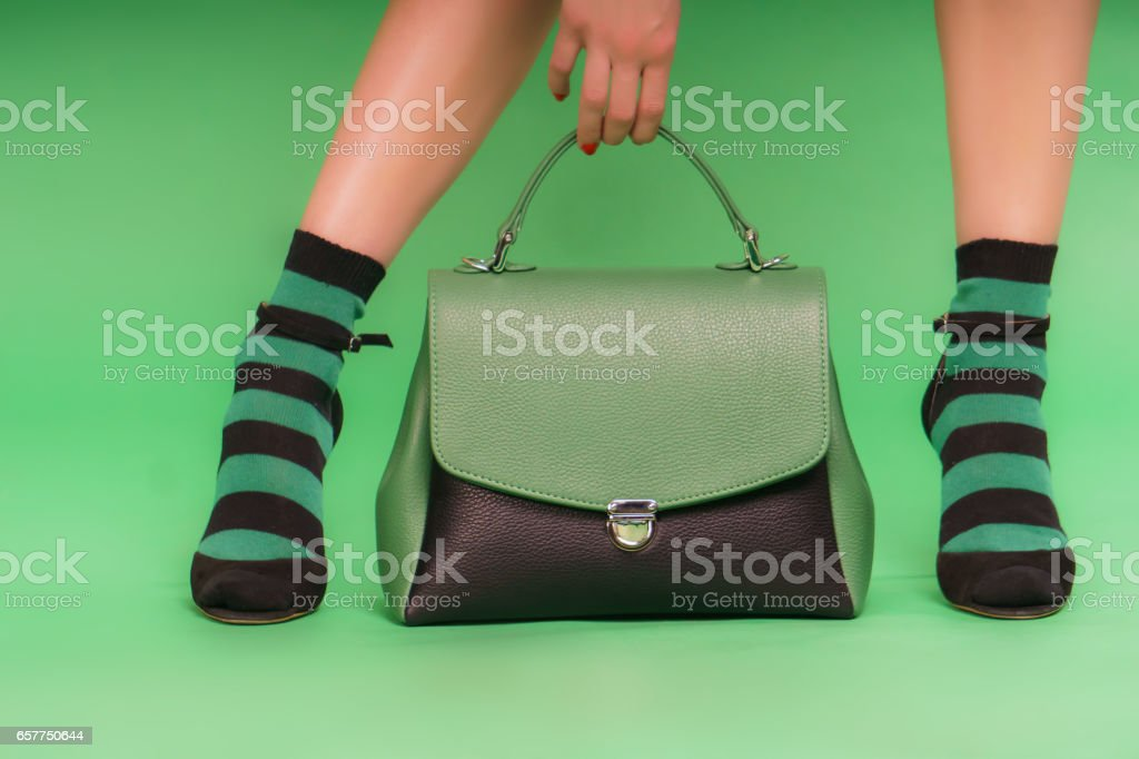 Green and black handbag on a green background stock photo