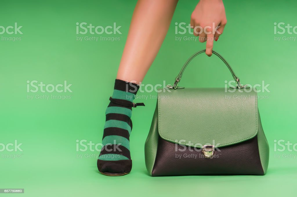 Green and black leather handbag stock photo