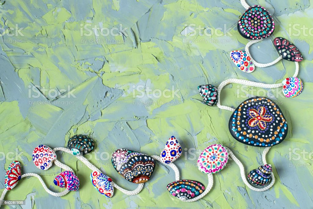 Green and blue background with hand-painted stones and seashells stock photo