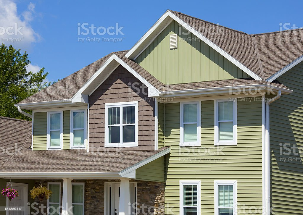 Green and Brown House of Stone, Cedar, Vinyl Siding stock photo