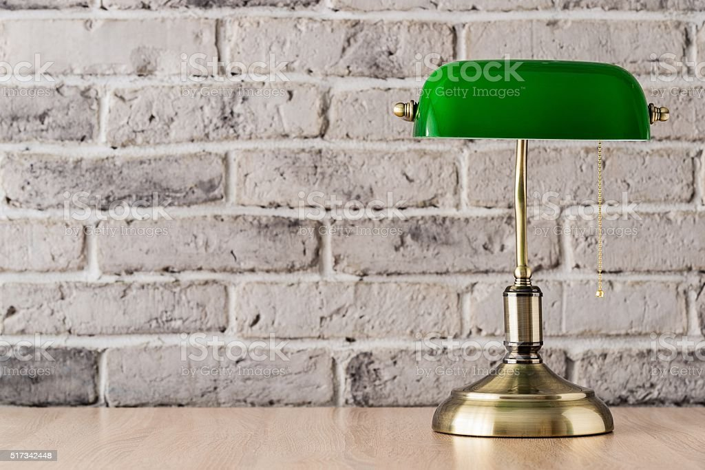 Green and gold banker lamp on the desk stock photo