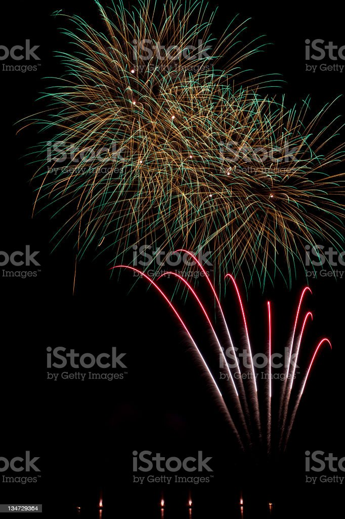 Green and gold fireworks on a lake with black sky royalty-free stock photo
