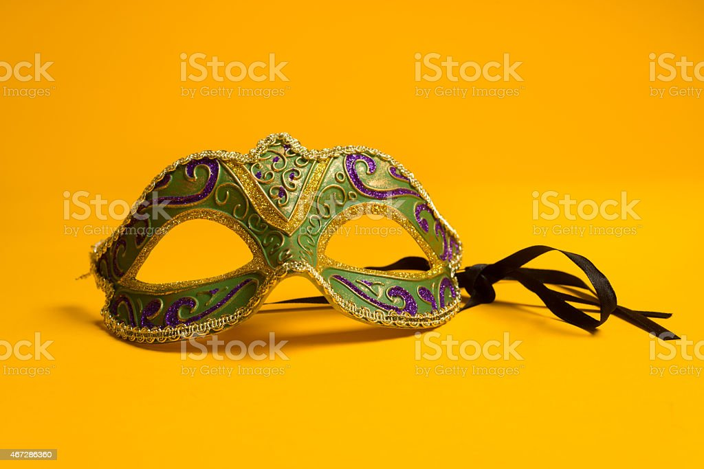 Green and gold Mardi Gras, venetian mask on Yellow background stock photo