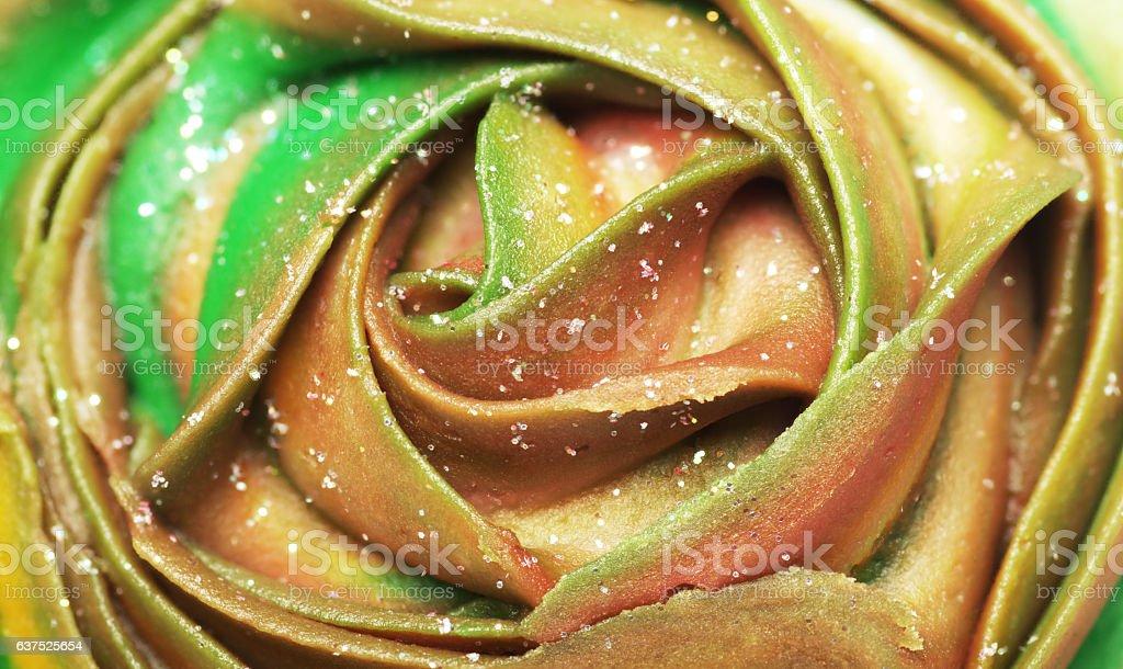 Green and orange creamy cupcake top close-up. stock photo